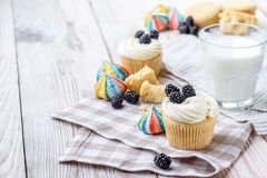 Vanilla cupcakes with blackberries and a glass of milk on a wooden background. On a napkin. Backlight. daylight Royalty Free Stock Photos