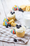 Vanilla cupcakes with blackberries and a glass of milk on a wooden background. On a napkin. Backlight. daylight Stock Image