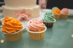 Vanilla cupcakes with bright cream glaze, close-up on a glass dish on the wedding table. Cake in the background, blur. The concept stock images