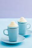 Vanilla cupcakes with buttercream topping on blue cups Stock Images