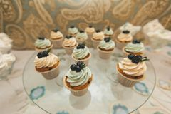 Vanilla cupcakes with cream icing, decorated with berries, close-up on a glass dish on the wedding table. The concept of food, royalty free stock photos