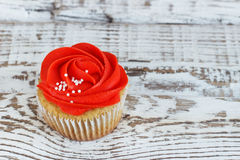 Vanilla cupcakes decorated with a red rose from a cream on a white background.  Royalty Free Stock Photography