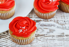 Vanilla cupcakes decorated with a red rose from a cream on a white background Stock Photo
