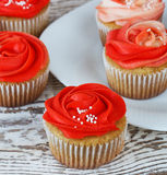 Vanilla cupcakes decorated with a red rose from a cream on a white background.  Stock Photos