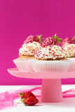 Vanilla cupcakes decorated strawberries on a pink backgground Royalty Free Stock Images