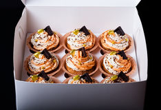 Vanilla cupcakes with orange and white creamcheese and chocolate. Decor stock images
