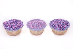 Vanilla cupcakes, with purple-coloured buttercream. Vanilla cupcakes, decorated with lavender-coloured buttercream and pink & purple sprinkles Royalty Free Stock Photography