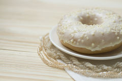 Vanilla donut and beads on a wooden backgroung Stock Image