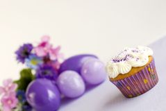 Vanilla Easter Cupcake with purple sprinkles. Vanilla Easter Cupcake with purple sugar sprinkles with selective focus, Easter eggs and flowers in background Royalty Free Stock Image