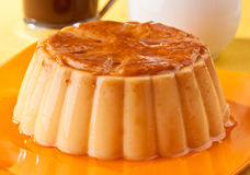 Vanilla flan. With coffee and milk, on yellow tablecloth Royalty Free Stock Images