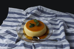 Vanilla flan served in glass dish on a kitchen cloth. With black background Royalty Free Stock Photo