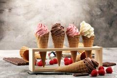 Vanilla frozen yogurt or soft ice cream in waffle cone. Vanilla frozen yogurt or soft ice cream in waffle cone and strawberry, raspberry and chocolate softice Stock Photos