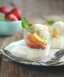 Vanilla ice cream with caramelized peaches Stock Photos