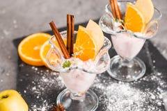 Vanilla Ice Cream With Fresh Mangoes on Black plate. Ice cream dessert, yogurt with orange slices, green mint leaves, cinnamon sti. Ice cream dessert, yogurt Stock Photo