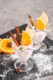 Vanilla Ice Cream With Fresh Mangoes on Black plate. Ice cream dessert, yogurt with orange slices, green mint leaves, cinnamon sti. Ice cream dessert, yogurt Stock Photos