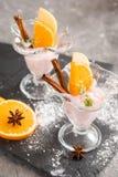 Vanilla Ice Cream With Fresh Mangoes on Black plate. Ice cream dessert, yogurt with orange slices, green mint leaves, cinnamon sti. Ice cream dessert, yogurt Royalty Free Stock Photo