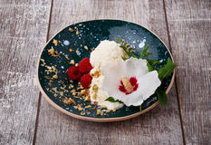 Vanilla ice cream with mint and pretty flower. A bowl of icecream and pink raspberries on a wooden background. Cold summer snacks. Stock Photos
