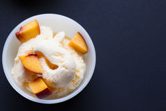 Vanilla ice-cream with peach. Selective focuse. Vanilla ice-cream with peach in white bowl. Selective focuse Stock Images