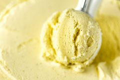 Vanilla ice cream scoop background. Summer food concept, copy space, top view. Scooped texture. Scooping out yellow ice Stock Photo
