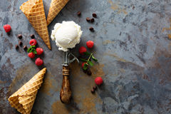 Vanilla ice cream scoop in a spoon. Perfect vanilla ice cream scoop in a spoon with waffles cones and fesh berries with copy space Royalty Free Stock Photography