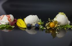 Vanilla ice cream scoops with strawberry syrop, blueberries, nuts and mango Royalty Free Stock Image