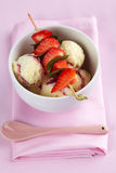Vanilla ice cream with strawberries and mint leaves on a skewer Royalty Free Stock Image