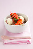 Vanilla ice cream with strawberries and mint leaves on a skewer Stock Images
