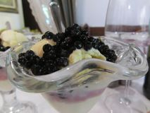 Vanilla ice cream with uncultivated bilberries or european blueberries in glass.  Stock Photos