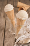 Vanilla ice cream in waffle cone on rustic wooden background, toned image Royalty Free Stock Image