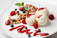 Vanilla ice cream and waffles with fresh berries. Scoops of vanilla ice cream and crisp golden waffles served with fresh raspberries and blueberries drizzled Royalty Free Stock Images