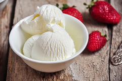 Vanilla ice-cream. In a white small bowl with fresh ripe strawberries on a wooden background. Rustic style and close up. Summer food concept royalty free stock images