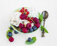 Vanilla icecream with chocolate flakes with berries and mint lea. Fresh vanilla icecream with chocolate flakes with raspberries, red currants and blueberries and royalty free stock image