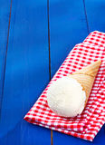 Vanilla icecream served in a cone. On a colourful red and white checkered napkin on rustic wooden boards with copyspace stock photo