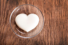 Vanilla jelly in the form of heart on a glass saucer close-up Royalty Free Stock Image