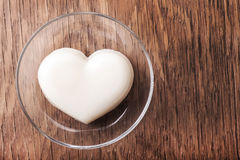Vanilla jelly in the form of heart on a glass saucer close-up Stock Photo