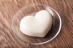 Vanilla jelly in the form of heart on a glass saucer Stock Image