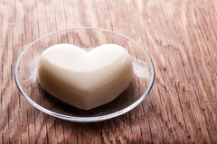 Vanilla jelly in the form of heart. On wooden background stock photography