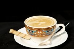 Vanilla latte coffee with wafer rolls with isolated black background