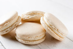 Vanilla macarons. On white wooden table Royalty Free Stock Images