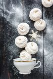 Vanilla marshmallow and snowflake falling into the cup. Royalty Free Stock Image