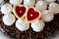 Vanilla meringue cookies and two sweet hearts Royalty Free Stock Images