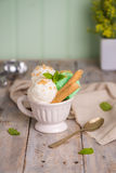 Vanilla and mint ice cream in cup. On wooden vintage style background Stock Photos