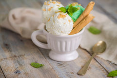 Vanilla and mint ice cream in cup. On wooden vintage style background Stock Photo
