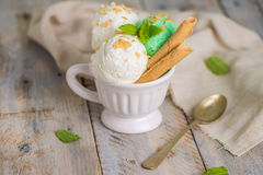 Vanilla and mint ice cream in cup. On wooden vintage style background Royalty Free Stock Photo