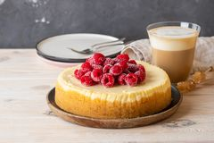 Vanilla New York cheesecake with raspberries and coffee with milk. Copy space. stock photo