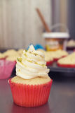 Vanilla pistachio gourmet cupcake with utensils in background Royalty Free Stock Photos