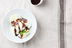 Vanilla and pistachio ice cream with chocolate sauce in a bowl on a plate on a linen textile Royalty Free Stock Image