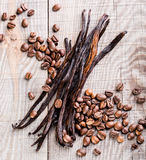 Vanilla pods and coffee beans. On wooden background Stock Photo