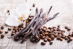 Vanilla pods and coffee beans. On wooden background Royalty Free Stock Photos