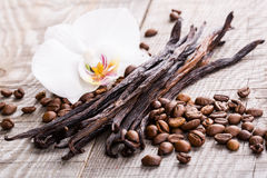 Vanilla pods and coffee beans. On wooden background Royalty Free Stock Photo
